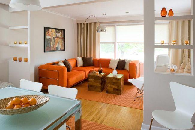 Помаранчевий кутовий диван і килим у вітальні
